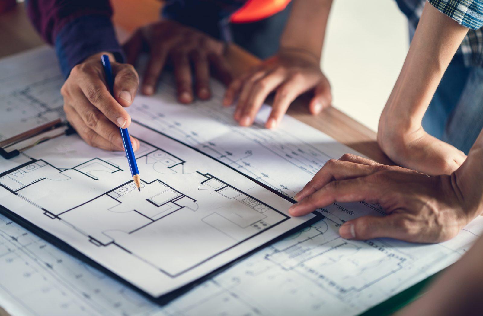 Prosjektmøte i byggebransjen der man ser på tegninger av våtrom.